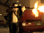 Niko fires an AK-47 from the cover of some parked cars.
