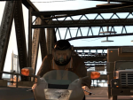 Niko rides a motorbike with a helmet on. A truck is see in in the background.