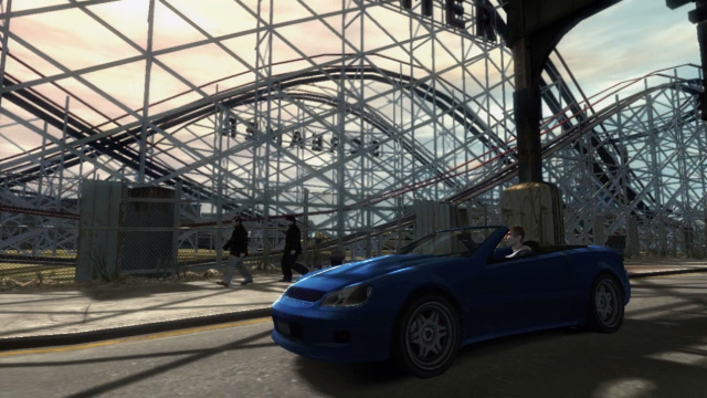 A blue sports car drives past a fairground.